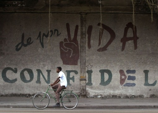 Cuban-cyclist-riding-past-Fidel-Castro-graffiti